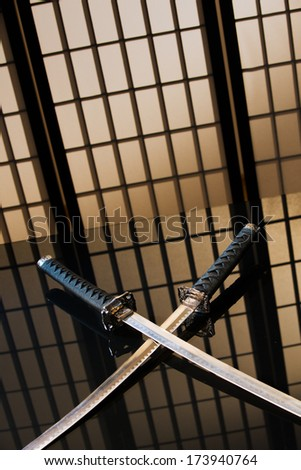 Katana and wakizashi with naked blades on a table in yellow room - stock photo