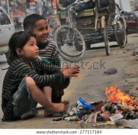 KATHMANDU - APRIL 27: Nepalese children after earthquake, near a campfire of rubbish, end of April 2015, Kathmandu, Nepal - stock photo