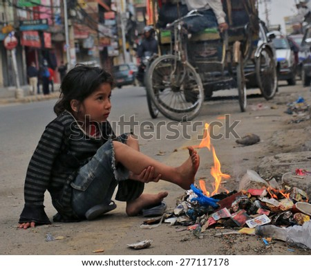 KATHMANDU - APRIL 27: Nepalese girl after earthquake, near a campfire of rubbish, end of April 2015, Kathmandu, Nepal - stock photo