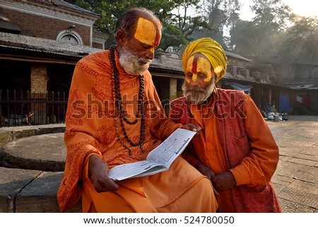 Kathmandu, Nepal - April 10, 2016: Hindu sadhu babas in saffron color clothing in ancient Pashupatinath Temple in Kathmandu, Nepal
