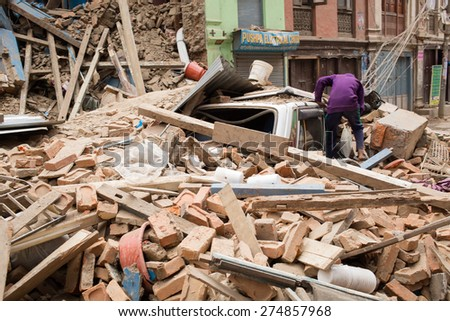 KATHMANDU, NEPAL - APRIL 25, 2015: Man tries to get inside a car under collapsed building after 7.8 earthquake in Nepal - stock photo