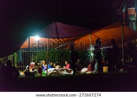KATHMANDU, NEPAL - APRIL 25, 2015: People prepare to sleep overnight on an open ground at Chuchepati after the 7.8 earthquake hit Kathmandu - stock photo