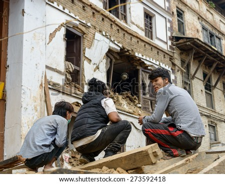 KATHMANDU, NEPAL - APRIL 26, 2015: Three young men squatting down on a pile of rubble at Durbar Square which was severly damaged after the major earthquake on 25 April 2015. - stock photo