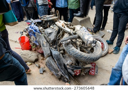 KATHMANDU, NEPAL - APRIL 26, 2015: Two crushed motorbikes next to the collapsed Dharhara tower after the major earthquake on 25 April 2015. - stock photo