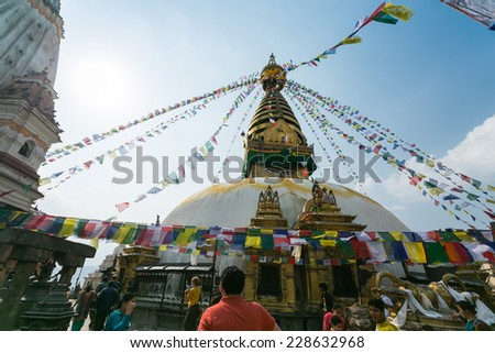 KATHMANDU, NEPAL - CIRCA MARCH 2014: People visit Swayambhunath or Monkey temple. The temple is protected as the UNESCO world heritage site. - stock photo