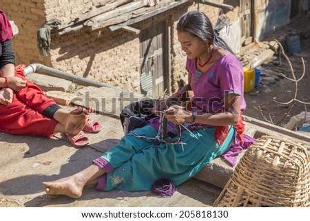 KATHMANDU, NEPAL - DEC 2, 2013: an unidentified girl sews a dress in the backyard on December 2, 2013 in Changu Narayan, Kathmandu valley, Nepal - stock photo