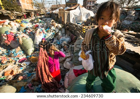 KATHMANDU, NEPAL - DEC 24, 2013: Unidentified child and his parents during lunch in break between working on dump. Only 35% of population Nepal have access to adequate sanitation. - stock photo