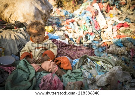 KATHMANDU, NEPAL - DEC 22, 2013: Unidentified child is sitting while her parents are working on dump. In Nepal 50,000 children die in 60% of cases from malnutrition. - stock photo