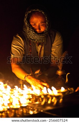 KATHMANDU, NEPAL - FEBRUARY 28: An unidentified tibetan woman lights incense butter candles in honor of Losar holiday on February 28, 2010 in Boudhanath, Kathmandu Valley, Nepal