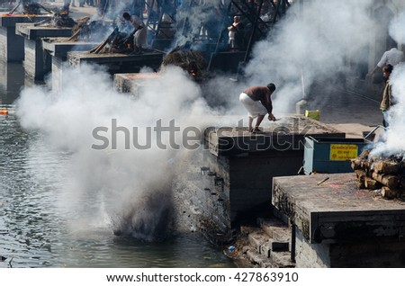 Kathmandu, Nepal - February 19, 2014: Cremation in Pashupatinath in Kathmandu, Nepal. The Hindu ritual of cremation in Pashupatinath Temple.