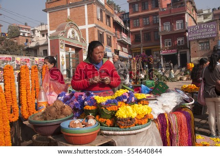 KATHMANDU, NEPAL, 3 FEBRUARY 2014: Women vendor selling marigold necklaces and religious tools at Pashupatinath Temple complex Kathmandu,  Pashupatinath Temple is a UNESCO World Heritage Site.