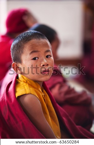 KATHMANDU, NEPAL - JANUARY 06: Little buddhist monk Dorje Tsering, 8, during puja ceremony in gelug-pa monastery on January 06, 2010 in Boudnath, Kathmandu Valley, Nepal. - stock photo