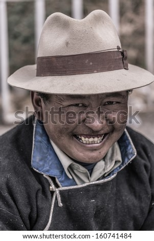 KATHMANDU, NEPAL, JULY 17: Portrait of an unidentified Tibetan man smiling and looking at the camera. There is a large community of Tibetan in Kathmandu since the invasion by China. Nepal 2013.