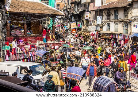 KATHMANDU, NEPAL - MARCH 23, 2014: The streets of kathmandu, Nepal, near Dubar square. Masses of people, rickshaws and Motorbikes crowd through the streets. - stock photo