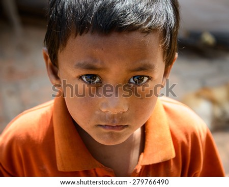 KATHMANDU, NEPAL - MAY 14, 2015: A young Nepalese boy living in a  makeshift campsite after two major earthquakes hit Nepal in the past weeks. - stock photo