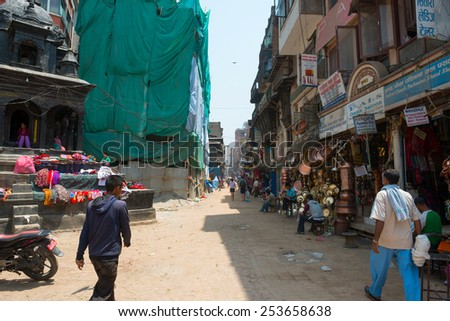 KATHMANDU, NEPAL - MAY 10, 2014: The streets near Dubar square of Kathmandu. Crowd of peoples, rickshaws and bikes moving through the streets - stock photo