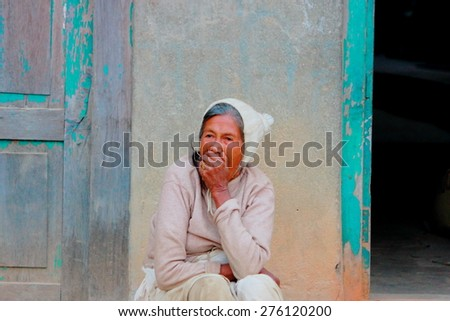 KATHMANDU,NEPAL-OCTOBER 15, 2012: Old woman yawning on the street waiting to grandchildren from schoolon October 15,Nepal. - stock photo