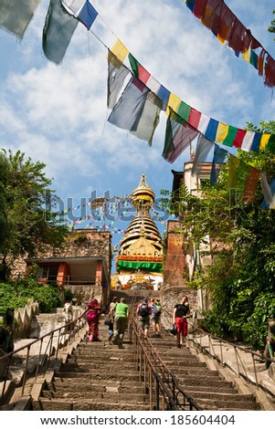KATHMANDU, NEPAL - SEPTEMBER 30, 2012 - Tourists walk up the stairs to the stupa Swayambunath - stock photo