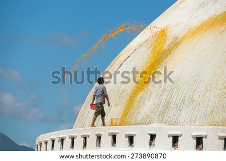 KATHMANDU - OCT 17: Nepali man throws color paint at the Boudhanath stupa on October 17, 2014 in Kathmandu, Nepal. Boudhanath stupa is the holiest Buddhist landmark in Nepal and UNESCO site since 1979