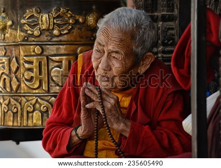 KATHMANDU - OCTOBER 16: Unidentified Tibetan pilgrim prays at Boudha stupa on October 16, 2014 in Kathmandu, Nepal. Devotees from all over the world visit this site for religious merit and good luck. - stock photo