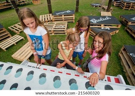 KATOWICE, POLAND - AUG 3: Unidentified children play piano outdoor during popular music festival OFF on August 3, 2014. Katowice lies within an urban zone, with a population of 2,746,460  - stock photo