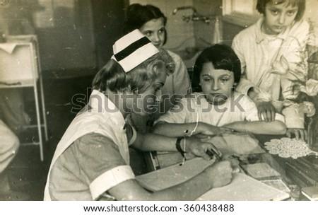 KATOWICE, POLAND, CIRCA 1939: Vintage photo of nurse working with children - stock photo
