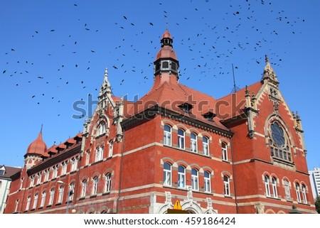 Katowice, Poland - high school building, old landmark. Black birds over city. - stock photo