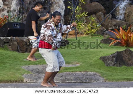 KAUAI, HAWAII - AUGUST 7: Aloha festival. Attractive young man in traditional dress performs Hawaiian dance on August 7, 2012 in Lihue, Kauai. - stock photo