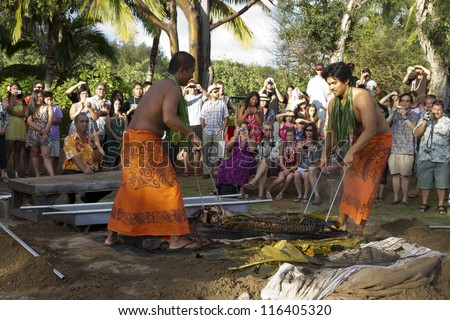 KAUAI, HAWAII - AUGUST 11: Aloha festival. Attractive young men in traditional Hawaiian dress prepare roast meat for luau on August 11, 2012 in Lihue, Kauai - stock photo