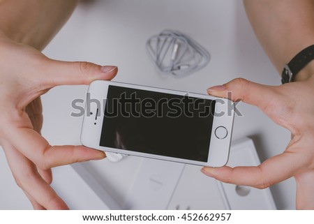 KAUNAS, LITHUANIA - JULY 14, 2016: Girl holding iPhone SE smartphone in hands. Unboxing new mobile phone. Isolated on white.