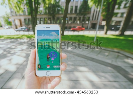 KAUNAS, LITHUANIA - JULY 18, 2016: Person holding mobile phone and playing Pokemon Go game. Pokemon Go is a location-based augmented reality mobile game.