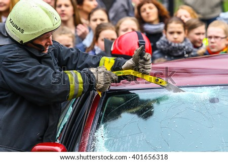 KAUNAS, LITHUANIA - MARCH 6, 2016: Fireman breaks the car's window. Fireman working in the car accident. Close up shot - stock photo
