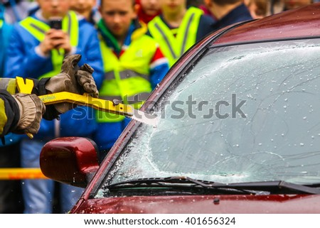 KAUNAS, LITHUANIA - MARCH 6, 2016: Fireman breaks the car's window. Fireman working in the car accident. Close up shot