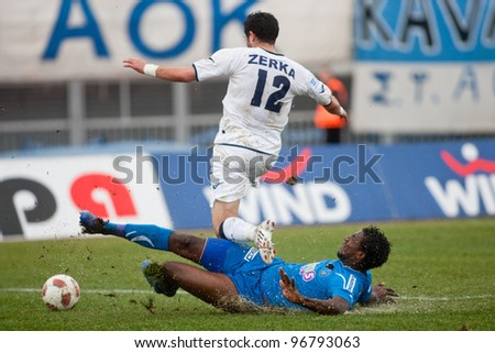 KAVALA, GREECE - JANUARY 23: Iraklis player Monsef Zerka (standing) fights for the ball with Kavala player Douglas Foureira (on the ground) during the Kavala vs Iraklis game at Kavala stadium on January 23, 2011 in Kavala, Greece