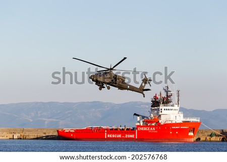 KAVALA, GREECE- JUNE 21, 2014: Apache AH-64 flying over energean ship during the Kavala Airshow 2014, in Kavala, Greece. - stock photo