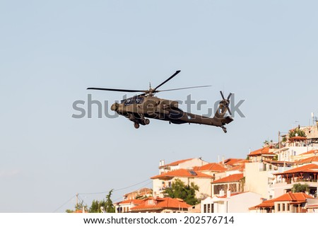 KAVALA, GREECE- JUNE 21, 2014: Apache AH-64 flying over houses during the Kavala Airshow 2014, in Kavala, Greece. - stock photo