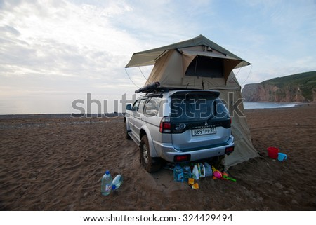 KAVALEROVO, RUSSIA - AUGUST 20, 2014: Mitsubishi Pajero Sport with rooftop tent on sandy beach - stock photo