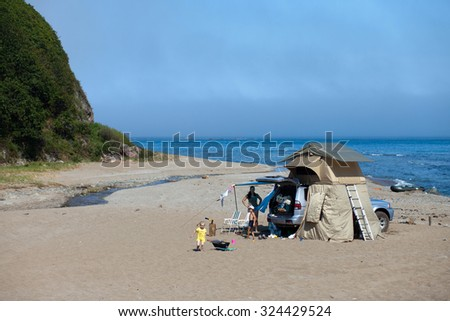 KAVALEROVO, RUSSIA - AUGUST 21, 2014: Mitsubishi Pajero Sport with rooftop tent on sandy beach. Camping life - stock photo
