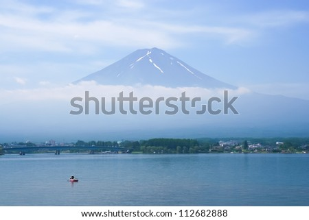 Kawaguchi Lake in front of mount Fuji and fisherman - stock photo