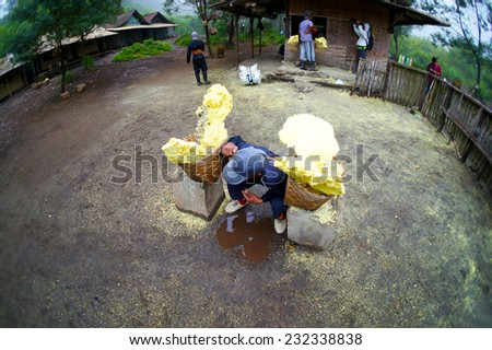 KAWAH IJEN, INDONESIA - APRIL 05: Worker carrying sulfur inside Ijen crater on April 05, 2013. Workers pick up the 60-90kg basket raw sulfur to be weighed.                               - stock photo