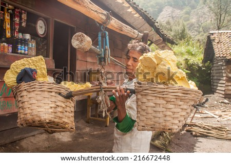 Kawah Ijen, Indonesia - April 24,2010 : Worker weighs sulfur inside Ijen crater  in Ijen Volcano, Indonesia. He carries the load of around 60kg to the top of the rip and then 3km down. - stock photo