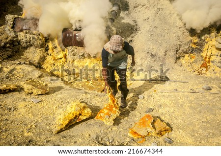 Kawah Ijen, Indonesia - April 24,2010 :  Workers extracting sulfur inside Ijen crater  in Ijen Volcano, Indonesia. He carries the load of around 60kg to the top of the rip and then 3km down. - stock photo