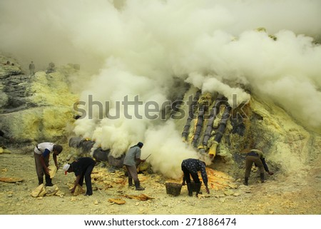 KAWAH IJEN, INDONESIA - AUGUST 10, 2011: Miners collect sulphur in the fumes of toxic volcanic gas at the sulphur mines in the crater of the active volcano of Kawah Ijen, East Java, Indonesia. - stock photo