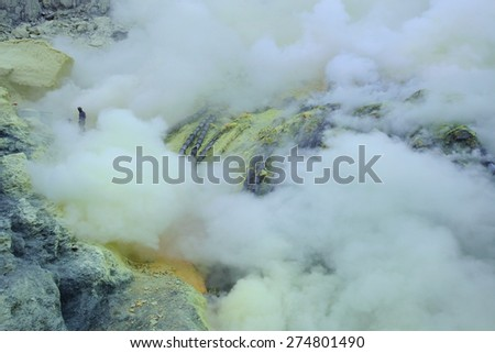 KAWAH IJEN, INDONESIA - AUGUST 8, 2011: Miners collect sulphur in the fumes of toxic volcanic gas at the sulphur mines in the crater of the active volcano of Kawah Ijen, East Java, Indonesia. - stock photo
