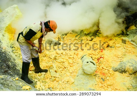 KAWAH IJEN, INDONESIA - JANUARY 22, 2013 : Miner collect sulfur (sulphur) in fumes of toxic volcanic gas from the sulfur mines in the crater of the active volcano of Kawah Ijen, East Java, Indonesia. - stock photo