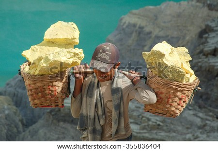 KAWAH IJEN, INDONESIA - OCT 16: Smiling Worker carries sulfur inside Kawah Ijen. Miners are extracting gaseous sulfur going out in the mine of the crater on OCT 16, 2010 in East Java, Indonesia  - stock photo