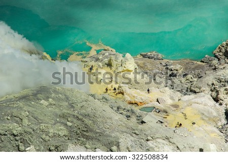 KAWAH IJEN, INDONESIA - OCT 16, 2010 : Unidentified people mining sulfur from the sulfur mines in the crater of the active volcano of Mt.Kawah Ijen on  OCT 16, 2010 in East Java, Indonesia - stock photo
