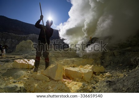 KAWAH IJEN, INDONESIA - OCT 12: Worker at sulfur mine inside Ijen crater on October 12, 2015. Miners are extracting gaseous sulfur going out in the mine of the crater - stock photo