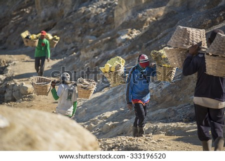KAWAH IJEN, INDONESIA - OCT 12,2015 : Worker carries sulfur inside Ijen crater in Ijen Volcano, Indonesia. Miners are extracting gaseous sulfur going out in the mine of the crater.