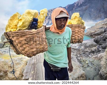 Kawah Ijen Volcano, East Java, Indonesia - May 25, 2013: Sulfur miner carrying baskets loaded with sulfur inside the crater of Kawah Ijen volcano on May 25, 2013, in East Java, Indonesia. - stock photo